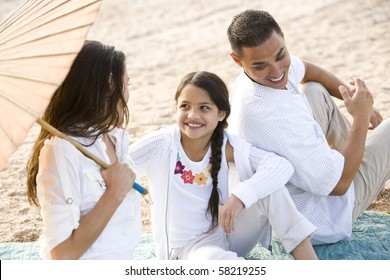 High angle view of happy Hispanic family with 9 year old daughter on beach