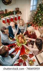 high angle view of happy large family holding christmas turkey together