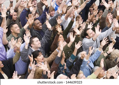 High angle view of happy multiethnic people raising hands together