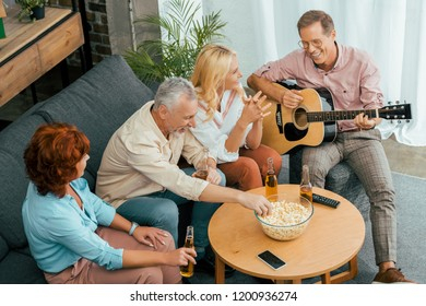high angle view of happy old friends spending time with guitar and beer at home