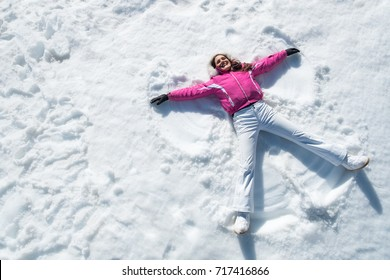 High angle view of happy woman lying on snow and moving her arms and legs up and down creating a snow angel figure. Smiling woman lying on snow in winter holiday with copy space.