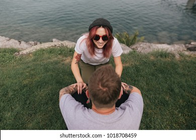 high angle view of happy young couple looking at each other while sitting on green grass near lake