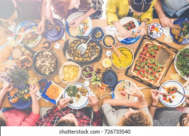 High angle view of house party of vegans cooking together at home and eating healthy organic meals made from local seasonal vegetables