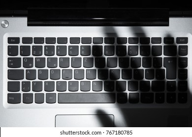 High Angle View Of Human Hand's Shadow Falling On Laptop Keypad