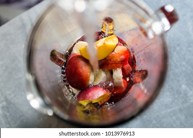 High angle view image of adding drinking water into a blender jar with sliced peach, banana and red berries. Share your recipes