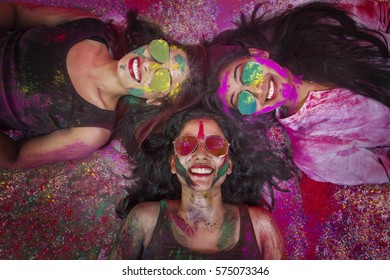 High angle view of indian teenage girls lying and covered in colored powder during holi color festival