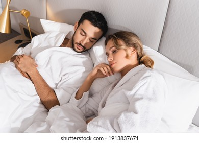 High angle view of interracial couple in bathrobes sleeping in hotel room