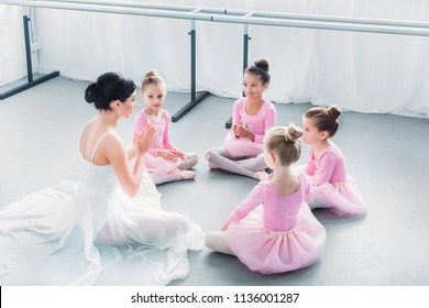 high angle view of kids in pink tutu skirts and young ballet teacher sitting together in ballet school