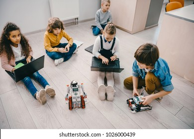 high angle view of kids programming robot while sitting on floor at stem education class