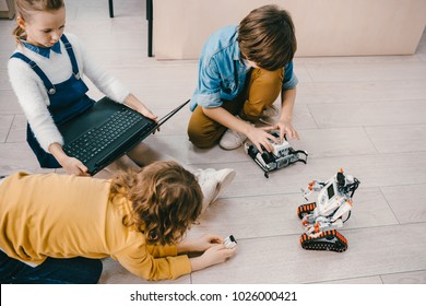 high angle view of kids sitting on floor at stem education class with robots and laptop