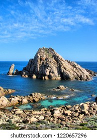 High angle view of a large granite rocky outcrop (locally known as Sugarloaf Rock) rising out of the Indian Ocean with blue / green rock pool in the foreground and blue sky with wispy white clouds beh
