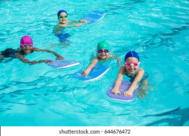 High angle view of little swimmers with kickboards enjoying in pool