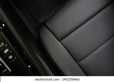 High angle view of luxury sport car front passenger seat and detail high end fabric and stitch texture along with blurred gear shift control buttons. Design element and car interior background. - Shutterstock ID 1901358466