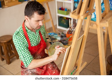 High angle view of a male artist wearing an apron and working on a painting in his studio