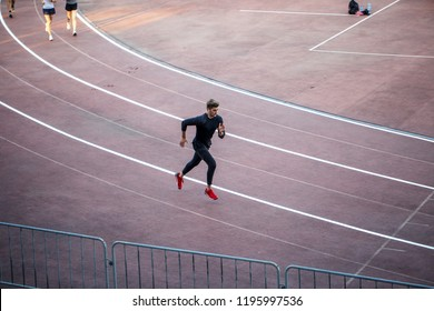 High angle view of male athlete running on race track in stadium