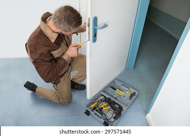 High Angle View Of Male Carpenter With Screwdriver Fixing Door Lock