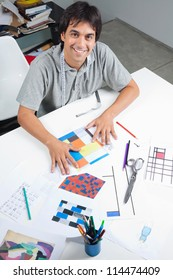 High angle view of male fashion designer sitting at table with outline designs and patterns at workshop