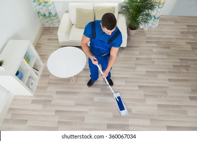 High angle view of male janitor cleaning hardwood floor with mop at home