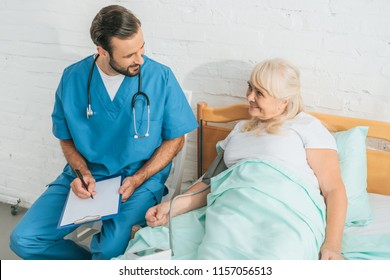 high angle view of male nurse writing on clipboard while measuring blood pressure to smiling senior woman lying in bed