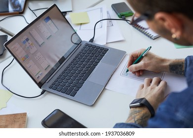 High angle view at male software engineer designing interface for mobile application or website, focus on laptop screen, copy space