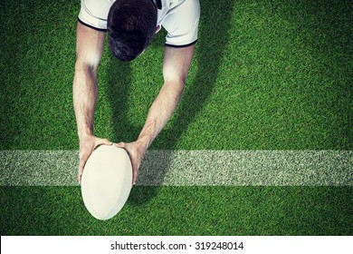 High angle view of man holding rugby ball with both hands against pitch with line