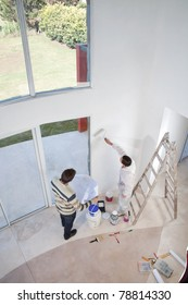 High angle view of man holding blueprint and workman painting the wall