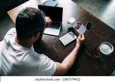 high angle view of man looking at photo of ex-girlfriend