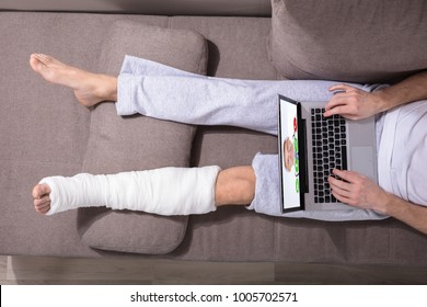 High Angle View Of A Man With Plastered Leg Video Conferencing With Doctor On Laptop