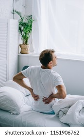 high angle view of man sitting on bed and suffering from back pain