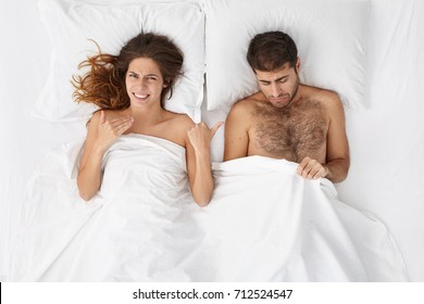 High angle view of married couple having problem in bed. Handsome man looking under blanket at his penis feeling unhappy, having erictal dysfunction, wife lying next to him and mocking at him
