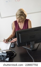 High angle view of mature businesswoman writing on document at computer table