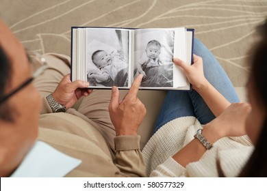 High angle view of mature father and his young daughter sitting in living room and leafing through photobook