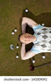 High angle view of mature man with balls and club lying on grass at golf course