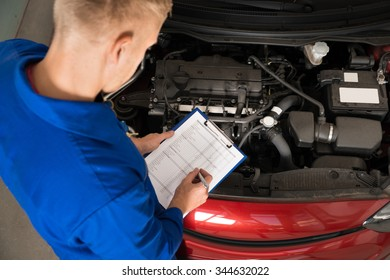 High Angle View Of A Mechanic Standing Near Car Writing On Clipboard In Garage