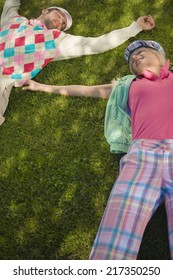 High angle view of a mid adult couple lying on grass
