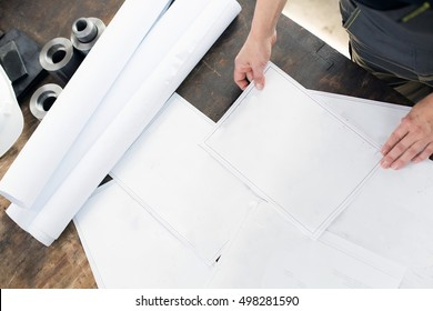 High angle view of mid adult architect with blueprints at table in industry