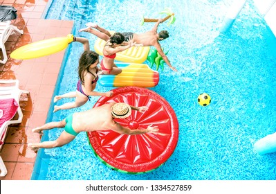 High angle view of millenial friends jumping at swimming pool party - Youth vacation concept with happy guys and girls having fun in summer day at luxury resort - Young people on warm bright filter