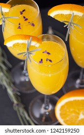High angle view of mimosa cocktails with orange juice and champagne decorated with lavender leaves and flowers and orange slices. Focus on the lavender flowers in the glass