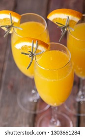 High angle view of mimosa cocktails with orange juice and champagne decorated with lavender leaves and flowers and orange slices