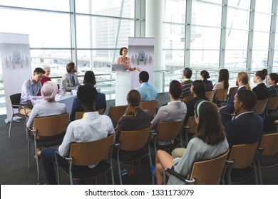 High angle view of mixed-race businesswoman speaking in front of business people sitting at seminar in office building