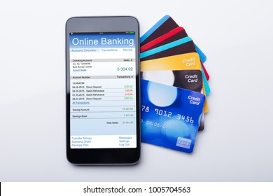 High Angle View Of Mobilephone With Online Banking App And Credit Card On White Background