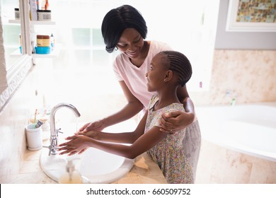 High angle view of mother and daughter washing hands at sink in bathroom