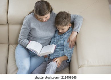 High angle view of mother and son reading book on sofa