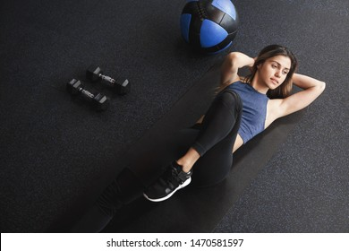 High angle view motivated woman workout, lying on rubber mat gym alone, look aside doing bicycle crunches smiling pleased feeling abs during training exercise with med-ball and dumbbells