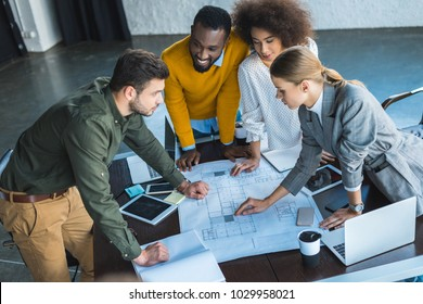high angle view of multicultural businesspeople with blueprint in office