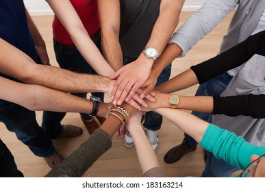 High angle view of multiethnic college students stacking hands in classroom