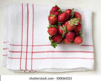 High angle view of natural looking strawberries in punnet on red and white dish towel