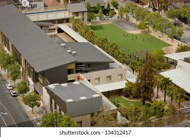 A high angle view of a new California elementary school, of modern architectural design with children playing on a grass field during recess.