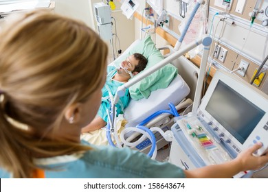High angle view of nurse pressing monitor's button with patient lying on bed in hospital