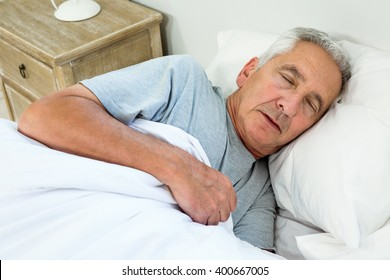 High angle view of old man sleeping on bed at home